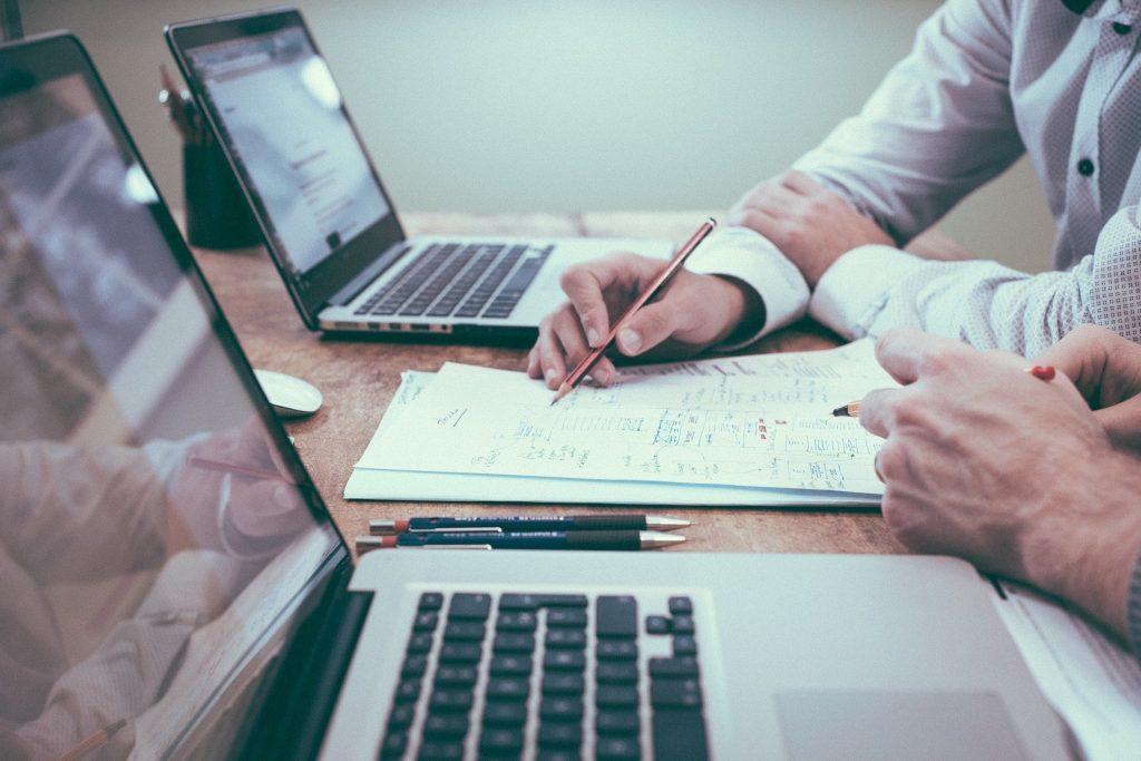 Deux personnes en réunion avec ordinateurs portables et papiers